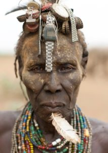 Ethiopia, Omo Valley, Omorate, Senior Dassanech Woman Wearing Watch As Headdress And Feather In The Chin
