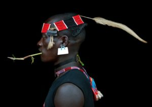 Ethiopia, Omo Valley, Key Afer, Bana Tribe Man Wearing A Headband With Feather, Strass Clips And Sim Card As Earring