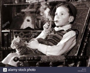 A young boy smoking a pipe and stroking a cat, sitting in a chair looking into the distance.