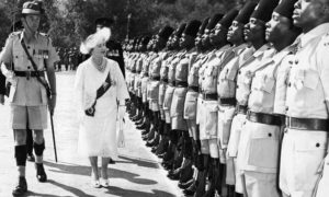 Queen Elizabeth, the Queen Mother accompanied by the guard commander Major R. Aikenhead, inspects a guard of honor of the Second Battalion the King's African rifles at the great Indaba in the Matotos Hills, near Bullawayo, Rhodesia on July 8, 1957. Behind the Queen Mother is her private secretary, Lt-Col. Gilliatt. The Queen Mother wears a jacket and dress of white lace. Her white hat is trimmed with white and sapphire blue osprey feathers. (AP Photo)